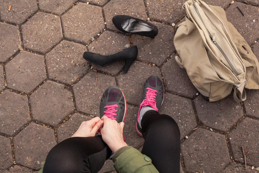 Woman puts on her running shoes instead of high heels.