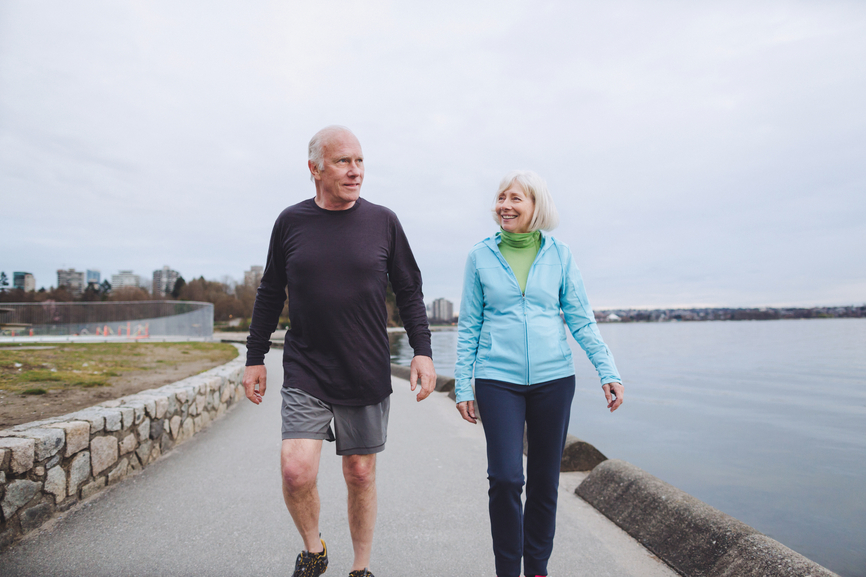 Happy senior couple exercising together outside - walking